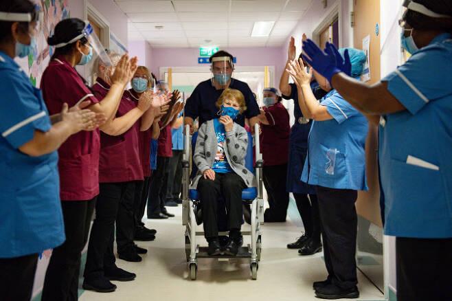 지난해 12월 8일 전 세계에서 가장 먼저 화이자 백신을 맞은 마거릿 키넌(91)이 의료진의 박수를 받으며 나오고 있다(사진=AFP)