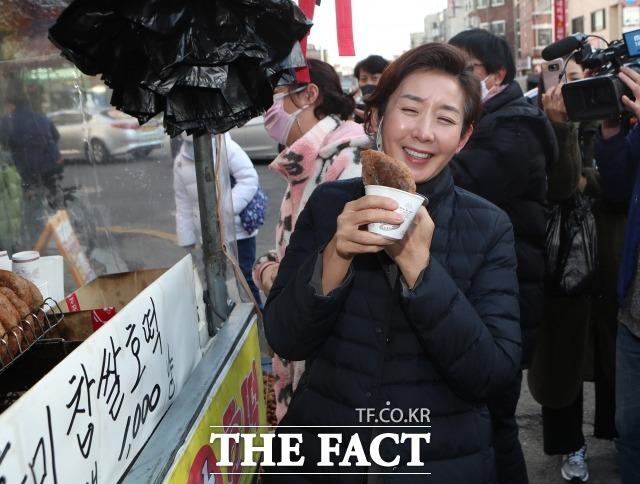나 전 의원은 그동안 고수했던 손질된 머리와 정장 대신 머리를 묶고, 편한 복장으로 이미지를 탈바꿈했다. 지난 20일 서울 양천구 신영시장을 방문해 호떡을 시식하며 웃는 나 전 의원. /국회사진취재단