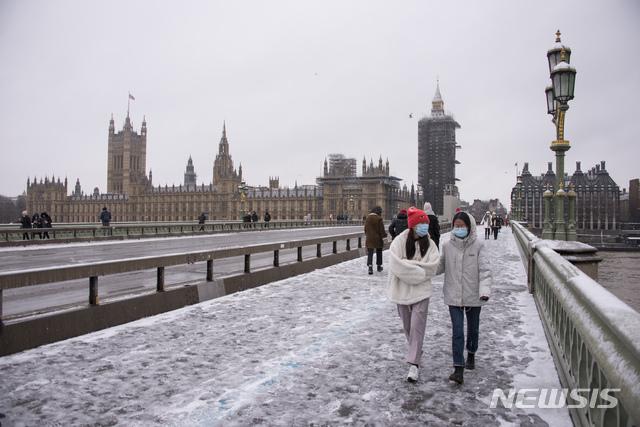 [런던=AP/뉴시스] 24일(현지시간) 신종 코로나바이러스 감염증(코로나19)이 확산하는 가운데 영국 런던의 웨스트민스터 다리에서 마스크를 착용한 사람들이 걷고 있다. 2021.01.24.