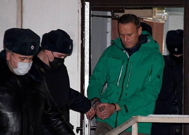 독극물 중독 치료 뒤 독일에서 귀국 직후 체포된 알렉세이 나발니가 지난 18일(현지시간) 30일간 구속하라는 법원의 판결 직후 수갑을 찬 채 경찰의 호위를 받으며 모스크바 외곽 힘키 경찰서 밖으로 나오고 있다. /AFP 연합뉴스