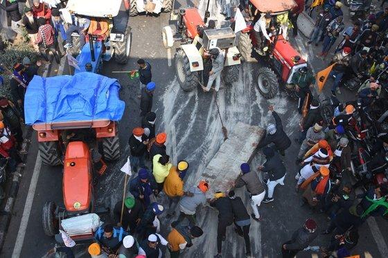 트랙터를 몰고 뉴델리에 진입한 농민들이 차단벽을 치우고 있다. AP=연합뉴스