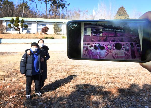 송 분교장과 경현군이 기념촬영을 하고 있다. 오른쪽 스마트폰에 표시된 1977년 당시 분교의 사진과 대비된다.