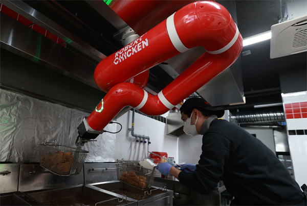 로봇이 치킨을 튀기는 `롸버트치킨`의 서울 강남구 개포동 매장에서 본지 조성호 기자가 `닭 튀기기` 대결을 벌이고 있다. 벽면에 고정된 로봇팔이 기름을 털어내는 작업을 하는 동안 조 기자도 닭고기가 서로 들러붙지 않도록 필사적으로 바구니를 흔들고 있다.  [한주형 기자]