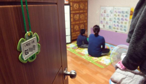 기초생활수급자인 김주연(가명)씨와 지난해 초등학교에 입학한 막내아들 동우(가명)가 서울 동대문구의 자택 벽에 붙여 놓은 한글과 숫자 판을 보고 있다. 동우네 가족은 한파가 거셌던 두 달여간 가스요금을 내지 못해 난방이 끊긴 방에서 지냈다.정연호 기자 tpgod@seoul.co.kr