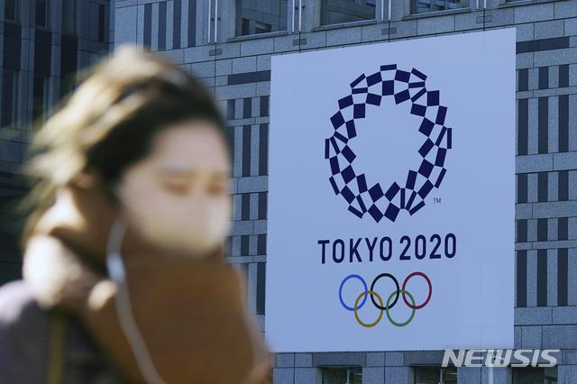 [도쿄=AP/뉴시스]지난달 19일 코로나19 예방을 위해 마스크를 쓴 한 여성이 일본 도쿄에서 2020 도쿄 올림픽 현수막 근처를 걷고 있다. 2021.01.19.