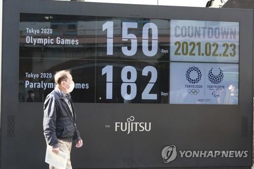 (도쿄 AP=연합뉴스) 일본 도쿄 시내에서 23일 한 행인이 하계 올림픽 개최가 150일 앞으로 다가왔음을 알리는 전광판 주변을 지나가고 있다. jsmoon@yna.co.kr