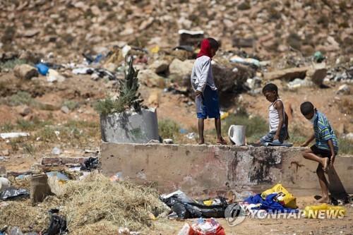 지난 9일 웨스턴케이프의 투브스리버에서 아이들이 쓰레기더미를 뒤지고 있다. [EPA=연합뉴스]