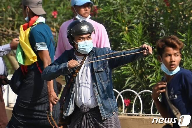 미얀마 양곤 등지에서 2021년 2월 25일 군정 지지자들이 등장해 새총과 칼, 파이프 등을 사용하며 시위대와 충돌했다. © AFP=뉴스1