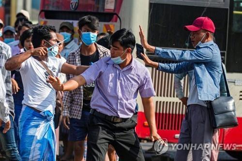 친군부 시위대가 시민들과 충돌하면서 흉기로 위협하는 모습. 2021.2.25 [로이터=연합뉴스]