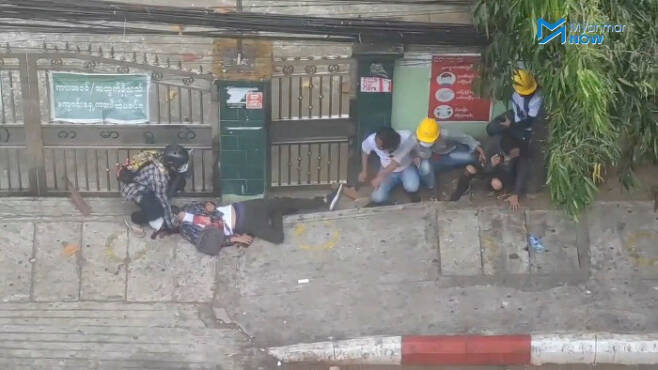주유엔 미얀마 대사 초 모 툰이 지난 26일(현지시간) 미국 뉴욕 유엔본부에서 열린 유엔총회에서 연설한 뒤 저항을 뜻하는 '세 손가락 경례'를 하고 있다(위 사진). 미얀마 최대 도시 양곤에서 28일 쿠데타 반대 시위에 참여했던 한 시민이 총에 맞아 쓰러지자 사람들이 상태를 살피고 있다.   뉴욕·양곤 | 로이터연합뉴스