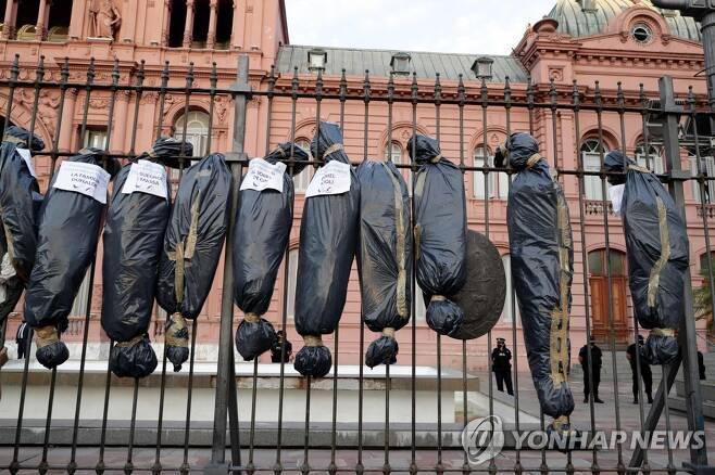 아르헨티나 대통령궁 앞에 시위대가 내건 시신백 모형. 정부 관계자들의 이름이 적혀있다. [AFP=연합뉴스]