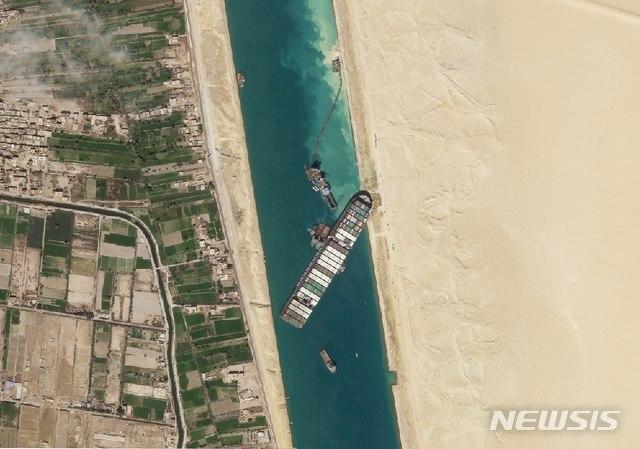 [수에즈=AP/뉴시스]플래닛 랩스의 위성 사진에 28일(현지시간) 이집트 수에즈의 수에즈 운하에 화물선 '에버 기븐'(Ever Given)이 갇혀 있다. 수에즈 운하를 가로막은 '에버 기븐'을 수로에서 꺼내기 위한 작업이 엿새째 이어지는 가운데 운하 관리 당국은 대형 예인선을 투입해 선체 부양 작업을 계속할 것이라고 밝혔다. 2021.03.29.