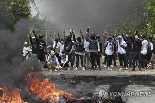 군경 무력진압에 '세 손가락 경례'로 맞서는 미얀마 시위대 (양곤 AP=연합뉴스) 27일(현지시간) 미얀마 양곤의 타케타 지역에서 군부 쿠데타 규탄 시위대가 저항을 상징하는 '세 손가락 경례'를 하며 무력진압에 나선 군경과 맞서고 있다. '미얀마군의 날'인 이날 쿠데타 규탄 시위대에 군경이 무차별 총격을 가해 100명이 넘는 시민들이 숨진 것으로 전해졌다. 이는 지난 2월1일 군부 쿠데타 발생 이후 하루 기준으로 최다 사망자 수다.