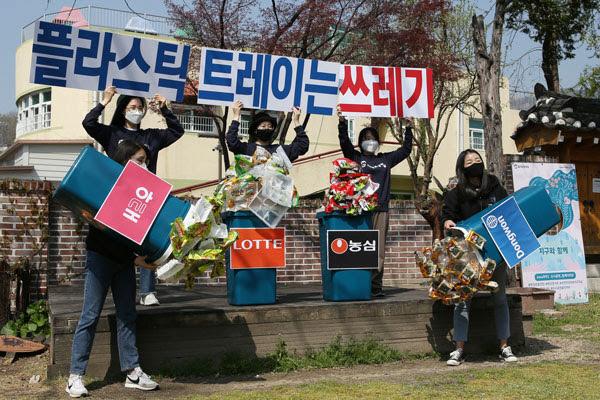 환경운동연합 활동가들이 7일 서울 종로구 환경운동연합 앞 마당에서 '플라스틱 트레이는 쓰레기' 퍼포먼스를 하고 있다. 4개의 쓰레기통에 식품제과기업들에서 나온 플라스틱 트레이와 비닐 포장재들이 가득 담겨 있다. 환경운동연합 제공