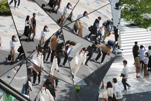 마스크를 쓴 시민들이 지난달 31일 일본 도쿄의 한 빌딩 벽에 있는 거울에 비치고 있다. 도쿄=AP 뉴시스