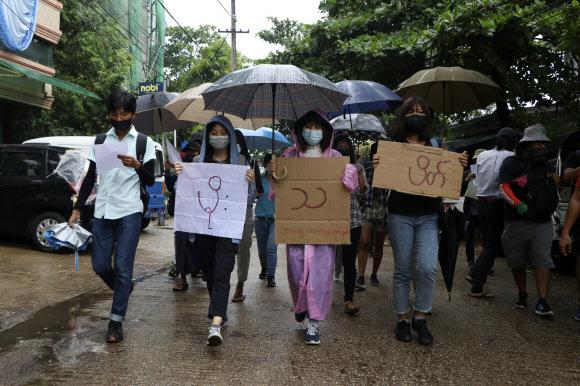 지난 6일(현지시간) 미얀마 양곤에서 우산을 쓴 반 쿠데타 시위대가 '빗물 시위'라고 쓰인 팻말을 들고 행진하고 있다.양곤=AP·뉴시스