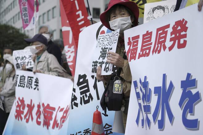 일본 정부의 후쿠시마 제1원전 오염수 바다 방류에 반대하는 일본 시민들이 13일 도쿄 총리관저 앞에서 연 집회에서 '오염수를 바다에 버리지 말라' 등이 적힌 펼침막을 들고 시위하고 있다. 도쿄/AP 연합뉴스