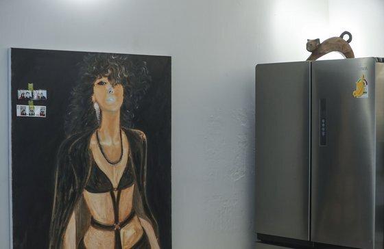 가수 김완선이 직접 그린 자화상 옆 냉장고 위에 목각으로 만든 고양이 장식품이 놓여 있다. 김성룡 기자