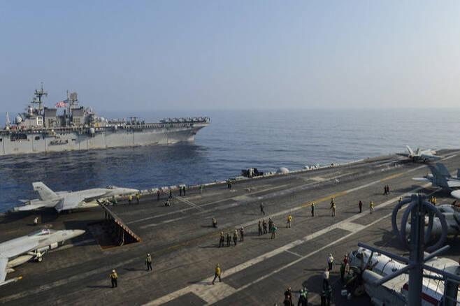 미 핵항모 시어도어 루즈벨트호에서 F-18 전투기가 이륙하고 있다. 옆에는 강습상륙함 마킨 아일랜드함이 항해하고 있다. 미 해군 제공