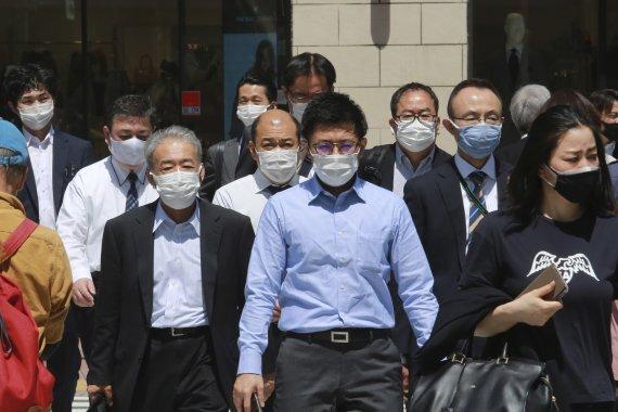 20일 도쿄에서 마스크를 쓴 사람들이 길을 건너고 있다. AP뉴시스