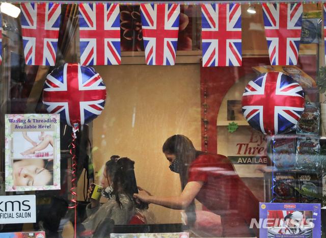 [런던=AP/뉴시스]영국 정부가 12일(현지시간) 코로나19 봉쇄를 단계적으로 완화하면서 런던의 한 미용실에서 한 여성이 머리를 손질하고 있다. 이에 따라 미용실, 상점, 체육관, 야외 술집 및 식당 등이 영업을 재개했다. 영국은 코로나19 백신 최소 1회 접종자가 전체 인구의 절반 정도인 3천200만 명에 달하는 것으로 나타났다. 2021.04.12.