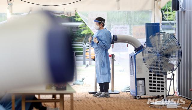 [서울=뉴시스]김병문 기자 = 낮 기온이 최고 28도까지 오르는 등 초여름 날씨를 보이는 22일 오후 서울 용산역 앞 코로나19 임시선별검사소에서 의료진이 에어컨 바람을 쐬고 있다. 2021.04.22. dadazon@newsis.com