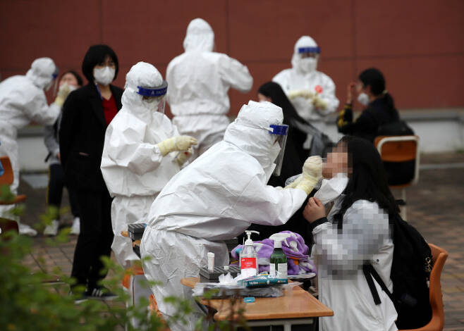 22일 광주 북구 한 고등학교에 마련된 임시선별진료소에서 학생들이 코로나19 검사를 받고 있다. 연합뉴스