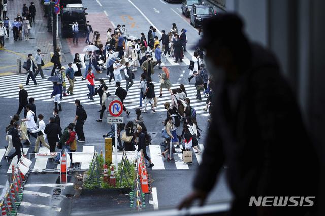 [도쿄=AP/뉴시스]지난달 29일 일본 도쿄 시부야 교차로를 한 남성이 창문 너머로 바라보고 있다. 221.05.07.