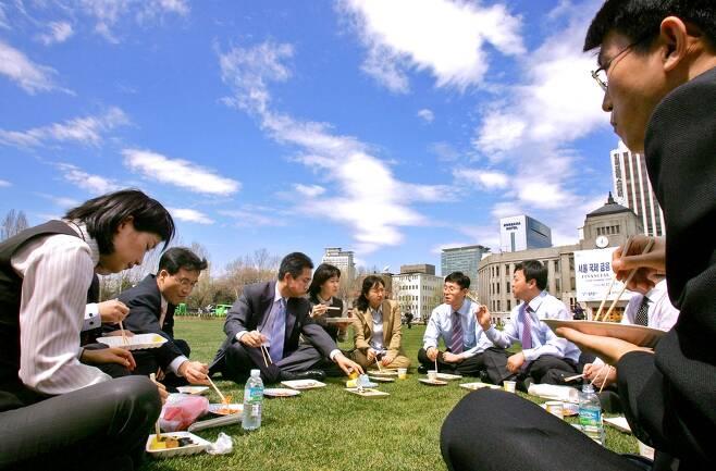 서울광장 잔디밭에 직장인들이 둘러앉아 도시락을 먹고 있다. 2006년 [연합뉴스 자료사진]