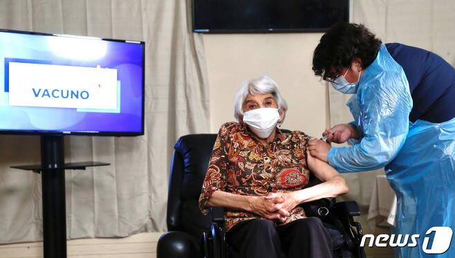 칠레 라세레나 노인요양원에서 2021년 1월 18일 라우라 아레유나(79)씨가 화이자 백신을 접종받고 있다. © 로이터=뉴스1 © News1 최서윤 기자