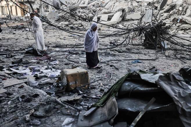 13일 팔레스타인 주민이 이스라엘군의 공격으로 파괴된 가자지구의 건물 잔해를 지나가고 있다. /AP 연합뉴스