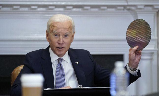 조 바이든 미국 대통령이 지난달 12일(현지시간) 미국 워싱턴 백악관 루즈벨트룸에서 열린 반도체 공급망 복원에 관한 최고경영자(CEO) 화상 회의에 참석해 실리콘 웨이퍼를 들어 보이고 있다.ⓒ뉴시스/AP