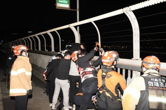 지난 1일 오전 서울 마포대교 북단 방향 근처에서 20대 남성이 투신하려는 것을 경찰관과 고등학생들이 붙잡아 구조하는 모습. 연합뉴스