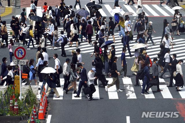 [도쿄=AP/뉴시스]14일 일본 도쿄에서 코로나19 확산을 막기 위해 마스크를 쓴 시민들이 건널목을 건너고 있다. 도쿄도는 14일 850명 이상의 코로나19 신규 확진자가 발생했다고 발표했다. 2021.05.14.