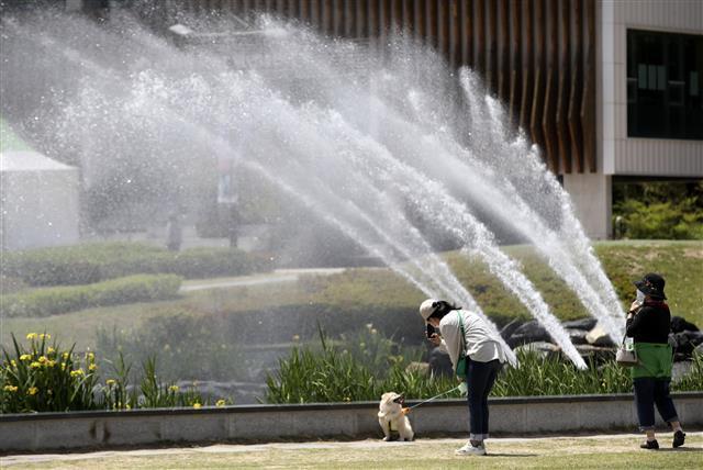 시원하게 뿜어져 나오는 물줄기 - 울산지역에 초여름 날씨를 보이는 13일 오후 울산 태화강 국가정원 오산못 분수대에서 뿜어져 나오는 물줄기 앞으로 산책을 하고 있다. 2021.5.13/뉴스1
