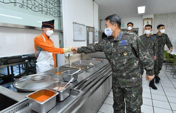 이성용 공군참모총장이 13일 공군 경북지역 방공관제부대를 찾아 격리 장병들의 식사 준비를 지원하는 병사를 격려하고 있다. 사진 공군.