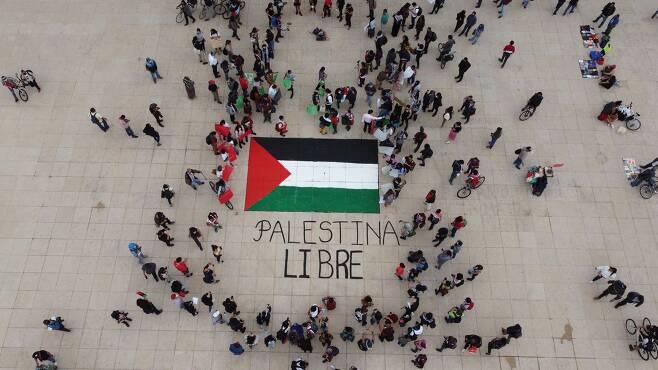 """멕시코 시티 시민들이 15일 팔레스타인 지지 집회를 열고 있다. 팔레스타인 깃발 아래 """"팔레스타인을 해방하라""""는 글씨가 보인다. EPA=연합뉴스"""