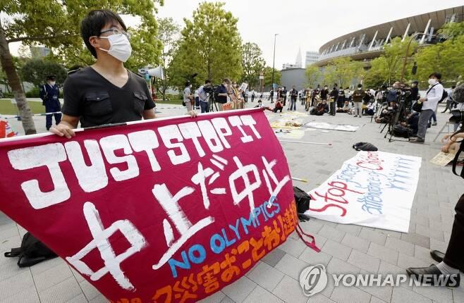 도쿄 올림픽 취소 촉구하는 시위대 (도쿄 로이터/교도=연합뉴스) 도쿄 올림픽 개최에 반대하는 일본 시민들이 9일 올림픽 육상경기 테스트 대회가 열린 도쿄 신주쿠(新宿) 국립경기장 주변에서 올림픽 취소를 촉구하는 시위를 벌이고 있다. jsmoon@yna.co.kr