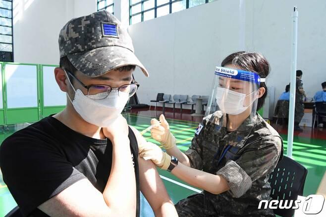 공군 제18전투비행단 30세 미만 장병들이 7일 기지 내 체육관에 마련된 예방접종센터에서 코로나19 화이자 백신을 맞고 있다. (공군 제공) 2021.6.7/뉴스1