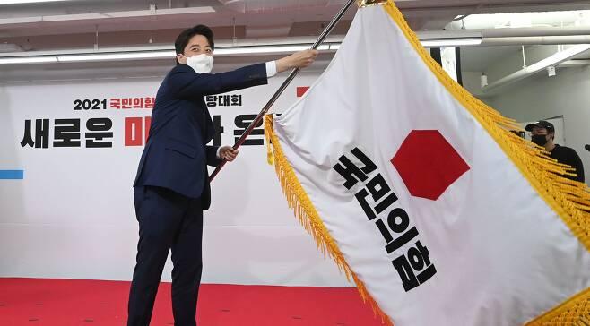 국민의힘 이준석 새 당 대표가 11일 서울 여의도 중앙당사에서 열린 전당대회에서 당기를 흔들고 있다. /연합뉴스
