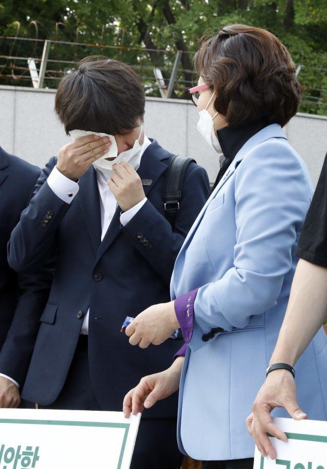 국민의힘 이준석 당대표 후보가 9일 서울 국방부 앞에서 피켓시위중인 천안함재단, 유가족회, 생존자전우회원들을 찾아 함께 피켓을 들고 있던 중 눈물을 닦고 있다. 뉴시스