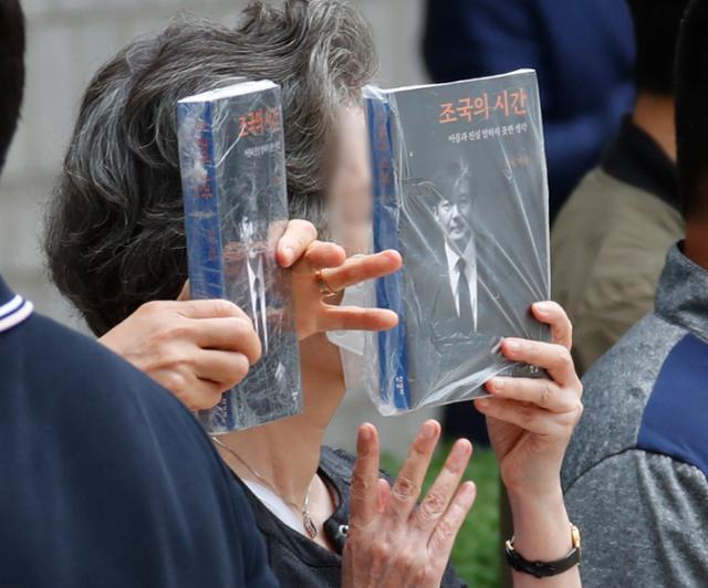 조국 전 법무부 장관이 11일 오전 서울 서초구 중앙지법에서 열린 공판에 출석하는 가운데 그의 지지자들이 신간 조국의 시간을 들고 조 전 장관을 응원하고 있다. 뉴스1