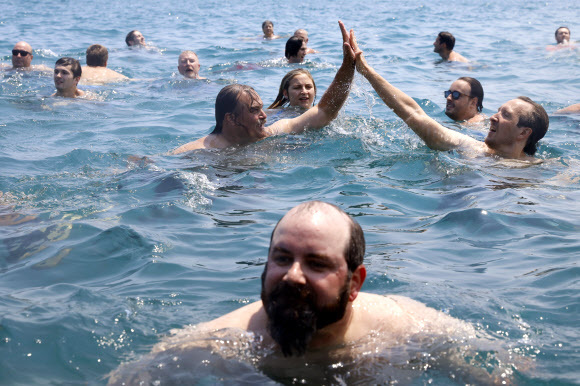 댄 오코너(뒤쪽 하이 파이브하는 이 가운데 왼쪽)가 365번째 다이빙에 성공한 뒤 함께 입수한 사람과 손을 맞부딪치고 있다.시카고 AP 연합뉴스
