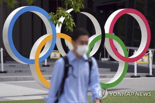 (도쿄 AP=연합뉴스) 2일 일본 도쿄도에서 마스크를 쓴 남성이 오륜 조형물 근처를 지나고 있다.