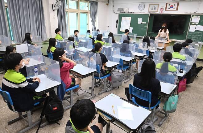 수도권 중학교의 등교 수업이 확대된 14일 오전 서울 양천구 월촌중학교에서 학생들이 수업 시작 전 담임교사로부터 방역 수칙을 교육받고 있다./사진공동취재단