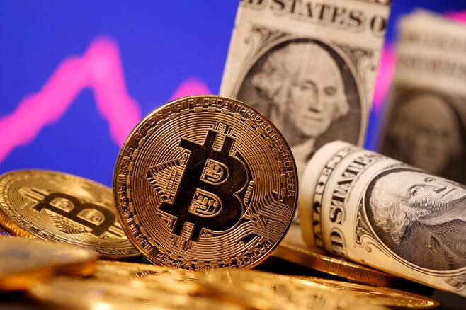 오는 9월부터 미국 달러와 함께 엘살바도르의 법정 통화가 될 비트코인 상징물이 달러 지폐와 나란히 놓여 있다. 로이터 연합뉴스