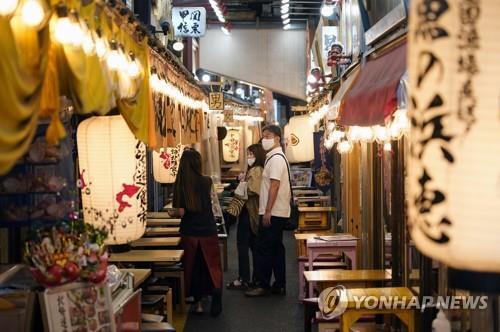 (도쿄 EPA=연합뉴스) 일본 10개 광역자치단체에 신종 코로나바이러스 감염증(코로나19) 긴급사태가 발효 중인 가운데 17일 오후 도쿄의 주점 사이로 마스크를 쓴 사람들이 이동하고 있다.