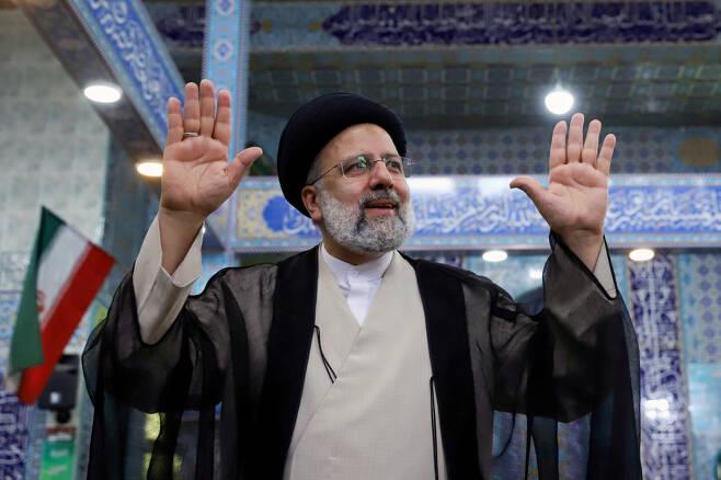 이란 대선에서 새 대통령으로 당선된 강경보수 성향 세예드 에브라힘 라이시가 지난 18일(현지시간) 이란 수도 테헤란의 한 투표소에서 투표를 마친 뒤 손을 흔들고 있다. [로이터]