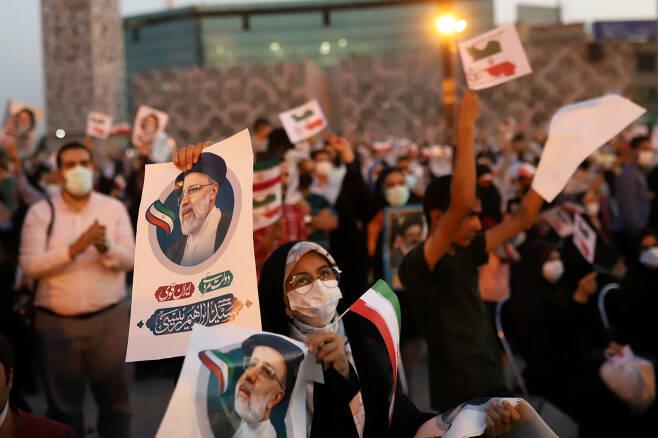 19일(현지시간) 이란 수도 테헤란에서 시민들이 새 대통령으로 당선된 강경보수 성향 세예드 에브라힘 라이시의 사진을 들고 환호하고 있다. [로이터]