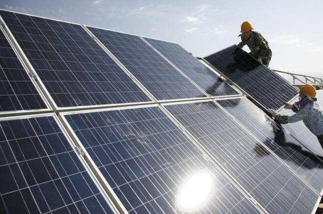 노동자들이 중국 신장 위구르 자치구 하미시의 태양광발전소에서 태양광 패널을 설치하고 있다. 중국 태양광 기업들이 신장의 위구르족을 강제 노동에 동원하는 것으로 알려지면서 미국과 EU(유럽연합) 등이 중국산 태양광 패널 소재의 수출 규제를 추진하고 있다.  /AP연합